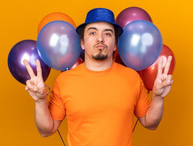 Zelfverzekerde jonge man met een feestmuts die vooraan ballonnen staat met een vredesgebaar geïsoleerd op een oranje muur