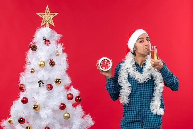 Zelfverzekerde jonge man met kerstman hoed en proeverij van een glas wijn en klok staande in de buurt van de kerstboom