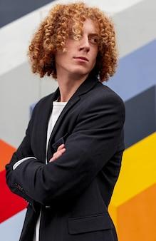 Zelfverzekerde jonge man met krullend rood haar die de armen kruist en wegkijkt terwijl hij tegen de muur staat met kleurrijke geometrische versiering op straat in de stad