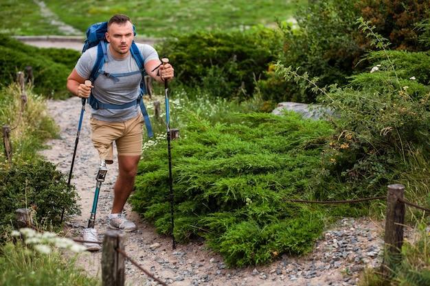 Zelfverzekerde jonge man met prothese die nordic walking doet terwijl hij een gezonde levensstijl leidt