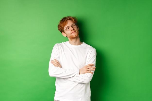 Zelfverzekerde jonge man met rood haar, bril, zelfvoldaan kijkend naar rechts kopie ruimte, kruis armen op borst zelfverzekerd, staande over groene achtergrond.