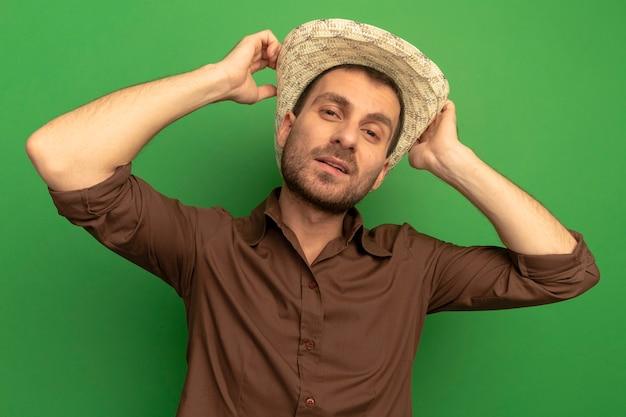 Zelfverzekerde jonge man met strandhoed kijken naar de voorkant aanraken van hoed geïsoleerd op groene muur