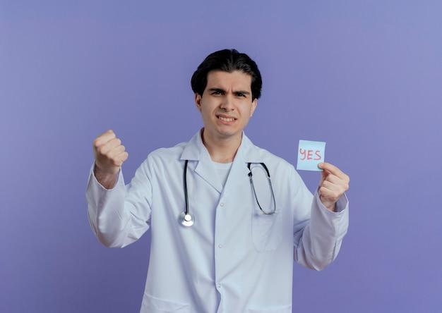 Zelfverzekerde jonge mannelijke arts die medische mantel en stethoscoop draagt die ja nota doet zijn sterk gebaar toont dat op purpere muur met exemplaarruimte wordt geïsoleerd