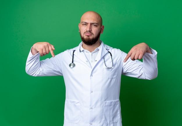 Zelfverzekerde jonge mannelijke arts die medische mantel en stethoscoop draagt, wijst naar zichzelf geïsoleerd op groene achtergrond