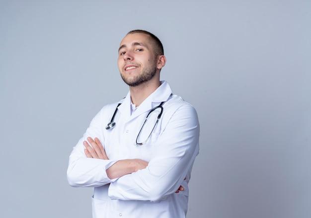 Zelfverzekerde jonge mannelijke arts die medische mantel en stethoscoop om zijn nek draagt ?? die zich met gesloten houding bevindt en glimlachend geïsoleerd op wit met exemplaarruimte