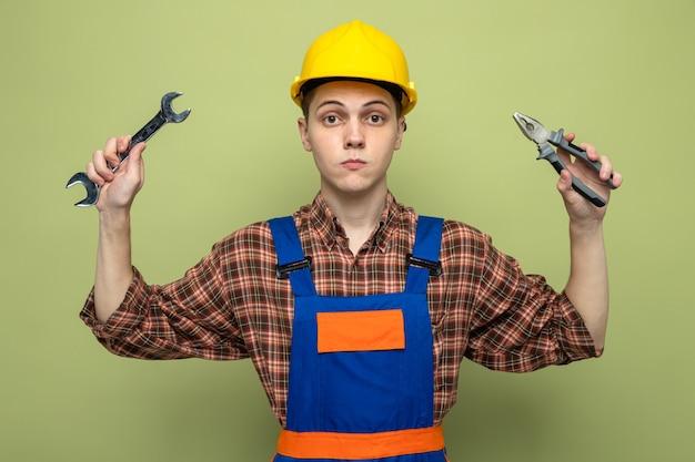 Zelfverzekerde jonge mannelijke bouwer die een uniform draagt met een steeksleutel met een tang