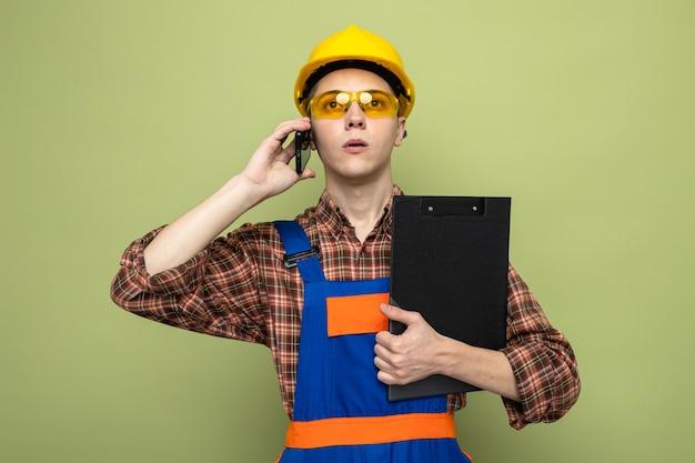 Zelfverzekerde jonge mannelijke bouwer met klembord in uniform met een bril spreekt op de telefoon