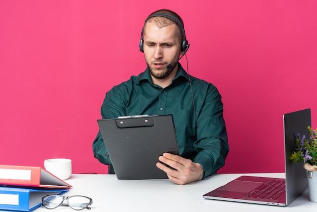 Zelfverzekerde jonge mannelijke callcenter-operator die een headset draagt die aan een bureau zit met kantoorhulpmiddelen die klembord vasthouden en bekijken