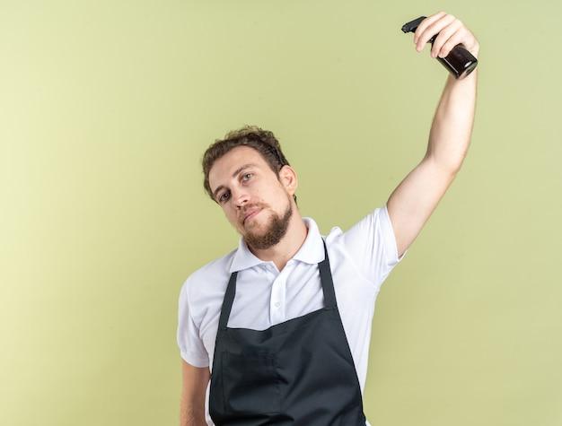 Zelfverzekerde jonge mannelijke kapper die een uniform draagt en zichzelf water geeft met een spuitfles geïsoleerd op een olijfgroene muur