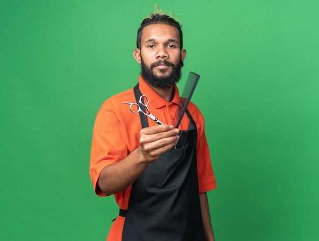 Zelfverzekerde jonge mannelijke kapper die uniform draagt en naar de voorkant kijkt, een schaar uitrekt en naar voren kamt, geïsoleerd op een groene muur met kopieerruimte
