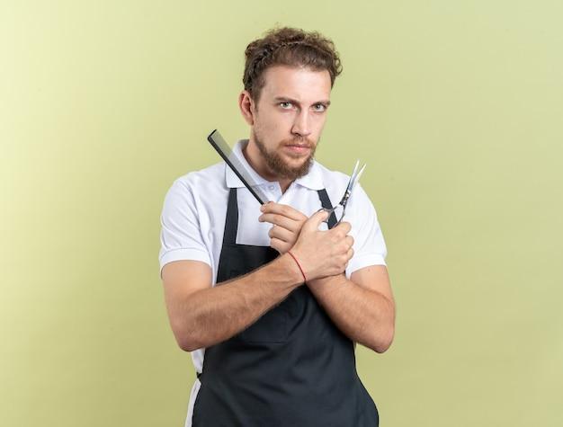 Zelfverzekerde jonge mannelijke kapper die uniform vasthoudt en sciccors kruist met kam geïsoleerd op olijfgroene muur