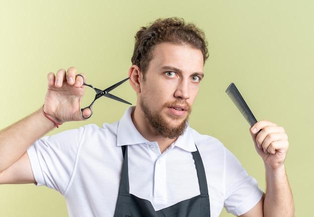 Zelfverzekerde jonge mannelijke kapper die uniforme scicors draagt met kam geïsoleerd op olijfgroene muur
