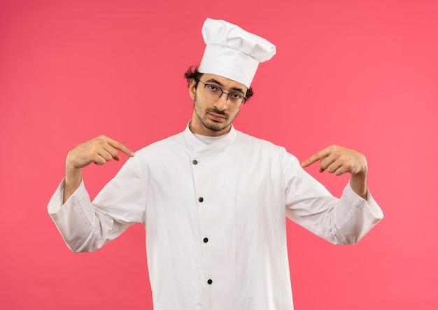 Zelfverzekerde jonge mannelijke kok die chef-kok uniform en glazen draagt, wijst naar zichzelf