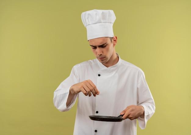 Zelfverzekerde jonge mannelijke kok die de koekenpan draagt die van de chef-kok eenvormige holding doet alsof morsen van zout op geïsoleerde groene muur met exemplaarruimte