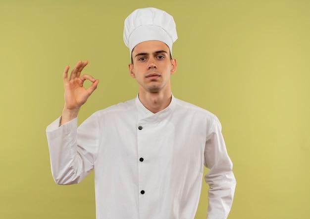 Zelfverzekerde jonge mannelijke kok die eenvormige chef-kok draagt die okgebaar op geïsoleerde groene muur met exemplaarruimte toont