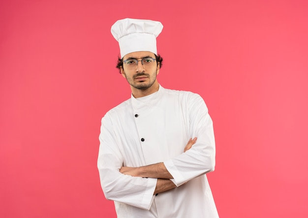 Zelfverzekerde jonge mannelijke kok die eenvormige chef-kok en glazen draagt die handen kruisen