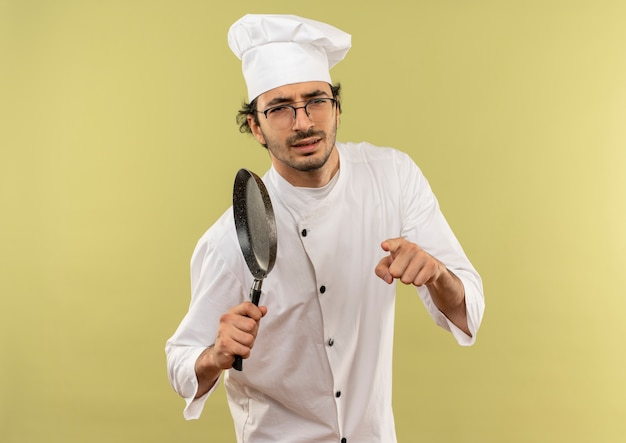 Zelfverzekerde jonge mannelijke kok die uniforme chef-kok en glazen draagt die koekenpan houdt en u gebaar toont