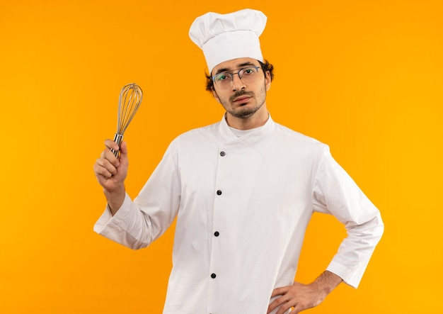 Zelfverzekerde jonge mannelijke kok dragen uniforme chef-kok en glazen houden zwaaien en hand op heup zetten