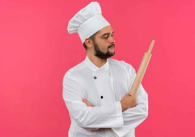 Zelfverzekerde jonge mannelijke kok in chef-kok uniform staande met gesloten houding en deegroller vasthoudend kijkend naar kant geïsoleerd op roze muur met kopieerruimte
