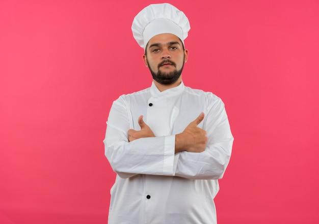 Zelfverzekerde jonge mannelijke kok in chef-kok uniform staande met gesloten houding geïsoleerd op roze muur met kopieerruimte copy