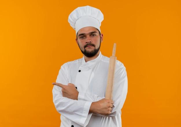 Zelfverzekerde jonge mannelijke kok in chef-kok uniform staande met gesloten houding met deegroller wijzend naar kant geïsoleerd op oranje muur met kopieerruimte