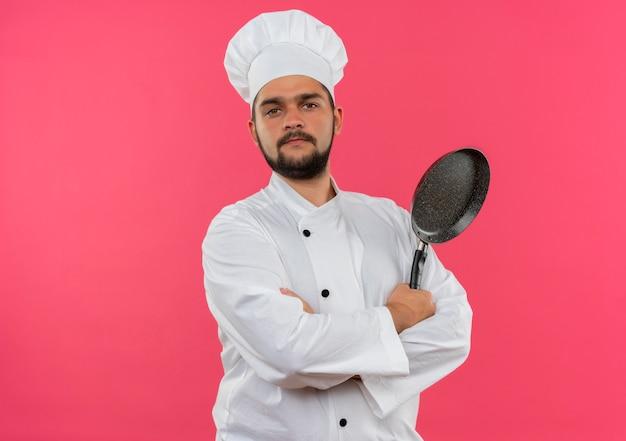 Zelfverzekerde jonge mannelijke kok in chef-kok uniform staande met gesloten houding met koekenpan geïsoleerd op roze muur met kopieerruimte