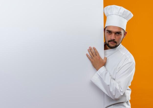 Zelfverzekerde jonge mannelijke kok in chef-kokuniform die achter staat en hand op een witte muur zet die op een oranje muur met kopieerruimte wordt geïsoleerd
