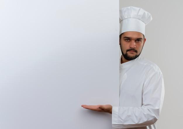 Zelfverzekerde jonge mannelijke kok in uniform van de chef-kok die achter staat en met de hand wijst naar een witte muur geïsoleerd op een witte muur met kopieerruimte