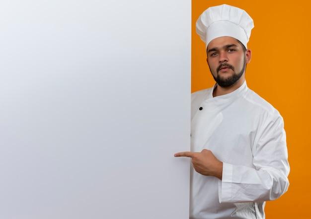 Zelfverzekerde jonge mannelijke kok in uniform van de chef-kok die achter staat en wijst naar een witte muur geïsoleerd op een oranje muur met kopieerruimte