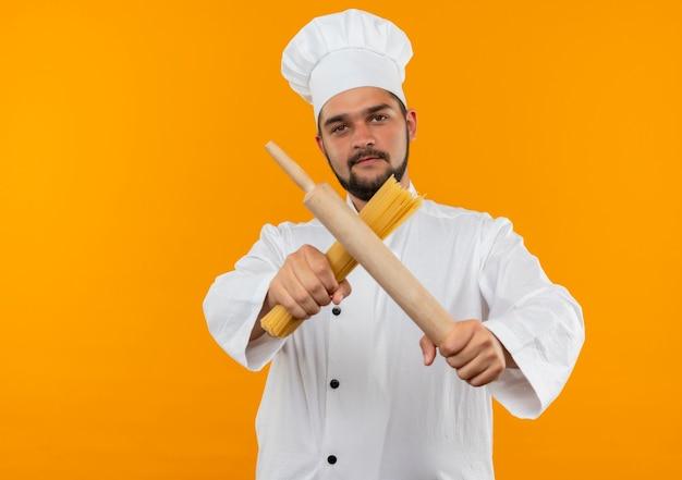 Zelfverzekerde jonge mannelijke kok in uniform van de chef-kok die deegroller en spaghetti pasta uitrekt naar geïsoleerd op oranje muur met kopieerruimte
