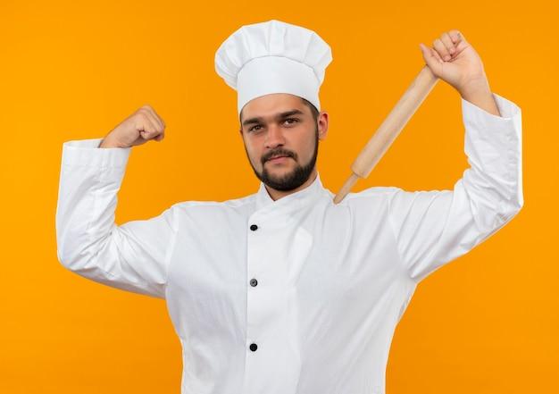 Zelfverzekerde jonge mannelijke kok in uniform van de chef-kok die deegroller op de schouder zet en sterk gebarend geïsoleerd op een oranje muur