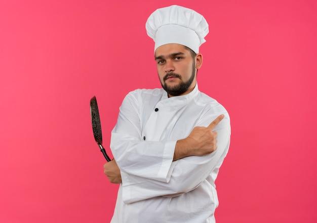 Zelfverzekerde jonge mannelijke kok in uniform van de chef-kok die een koekenpan vasthoudt en naar de zijkant wijst, geïsoleerd op een roze muur met kopieerruimte