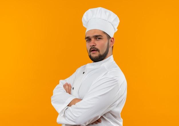 Zelfverzekerde jonge mannelijke kok in uniform van de chef-kok die in profielweergave staat met gesloten houding geïsoleerd op een oranje muur met kopieerruimte