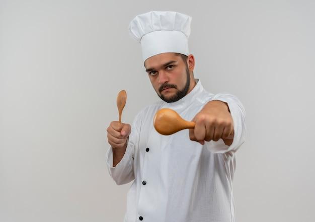 Zelfverzekerde jonge mannelijke kok in uniform van de chef-kok die lepels vasthoudt en uitrekt, geïsoleerd op een witte muur met kopieerruimte