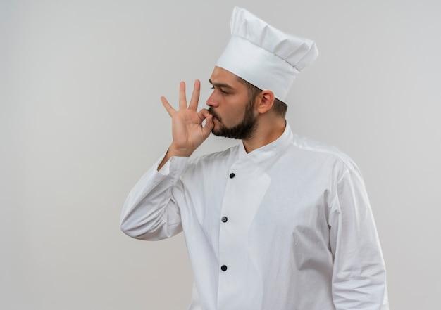 Zelfverzekerde jonge mannelijke kok in uniform van de chef-kok die naar de zijkant kijkt en een smakelijk gebaar doet dat op een witte muur met kopieerruimte wordt geïsoleerd