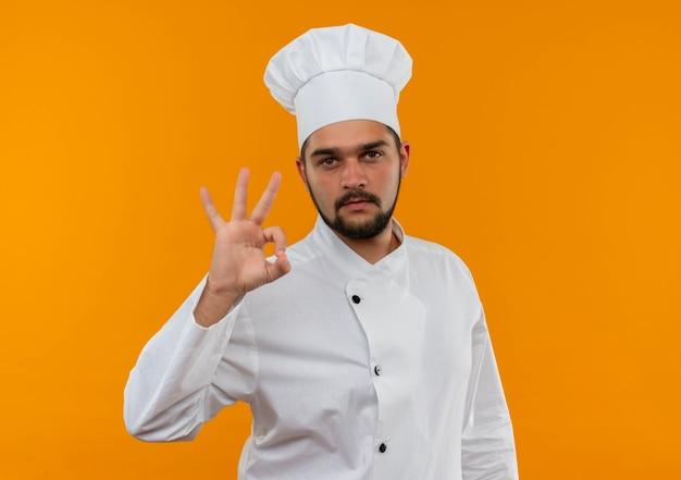 Zelfverzekerde jonge mannelijke kok in uniform van de chef-kok die ok teken doet en geïsoleerd op een oranje muur kijkt met kopieerruimte
