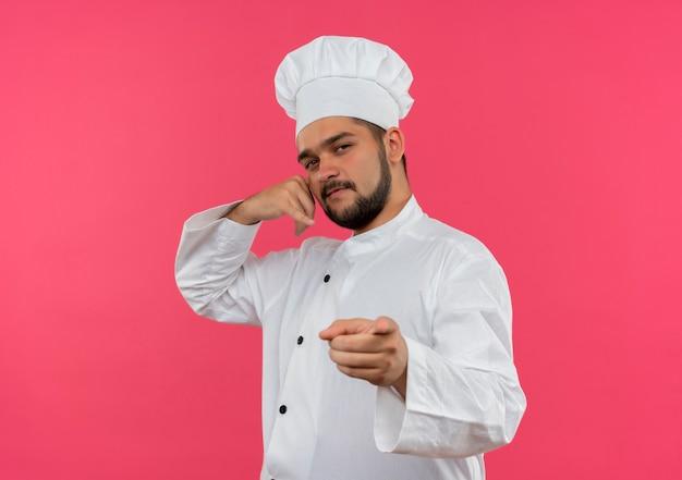 Zelfverzekerde jonge mannelijke kok in uniform van de chef-kok die oproepgebaar doet en geïsoleerd op roze muur wijst met kopieerruimte