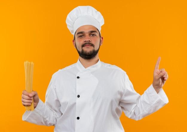 Zelfverzekerde jonge mannelijke kok in uniform van de chef-kok die spaghetti pasta vasthoudt en omhoog wijst geïsoleerd op een oranje muur