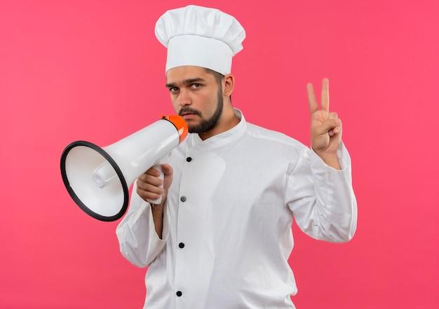 Zelfverzekerde jonge mannelijke kok in uniform van de chef-kok die spreker vasthoudt en vredesteken doet geïsoleerd op roze muur