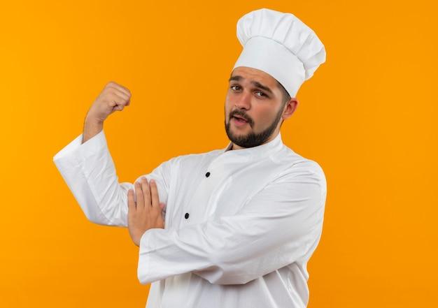 Zelfverzekerde jonge mannelijke kok in uniform van de chef-kok die sterk gebaart en zijn spieren aanraakt die op een oranje muur zijn geïsoleerd