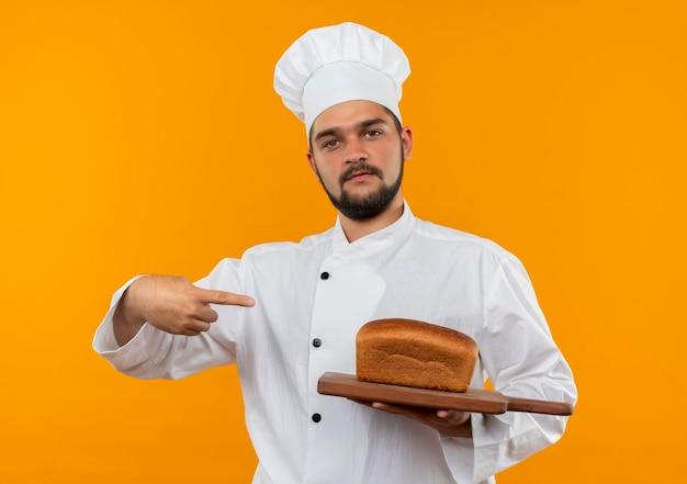 Zelfverzekerde jonge mannelijke kok in uniform van de chef-kok die vasthoudt en wijst op een snijplank met brood erop geïsoleerd op een oranje muur