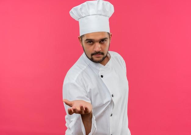 Zelfverzekerde jonge mannelijke kok in uniform van de chef-kok die zijn hand uitstrekt geïsoleerd op roze muur met kopieerruimte