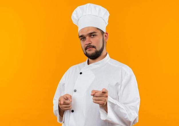 Zelfverzekerde jonge mannelijke kok in uniform van de chef-kok doet je gebaar geïsoleerd op een oranje muur met kopieerruimte Gratis Foto
