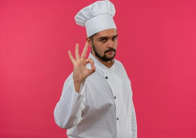 Zelfverzekerde jonge mannelijke kok in uniform van de chef-kok doet ok teken geïsoleerd op roze muur met kopieerruimte