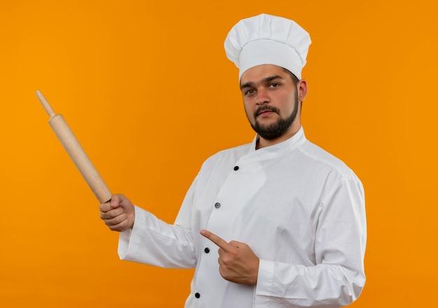 Zelfverzekerde jonge mannelijke kok in uniform van de chef-kok met deegroller en wijzend naar de zijkant geïsoleerd op een oranje muur