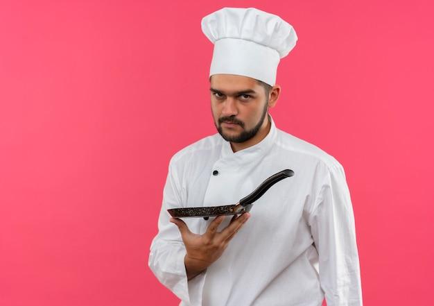 Zelfverzekerde jonge mannelijke kok in uniform van de chef-kok met koekenpan geïsoleerd op roze muur met kopieerruimte