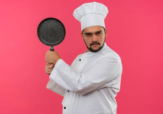 Zelfverzekerde jonge mannelijke kok in uniform van de chef-kok met koekenpan geïsoleerd op roze muur