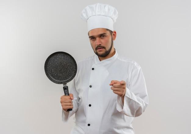 Zelfverzekerde jonge mannelijke kok in uniform van de chef-kok met koekenpan wijzend op een witte muur