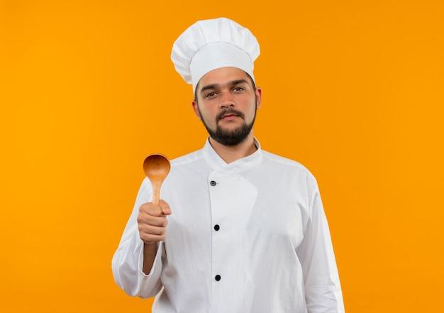 Zelfverzekerde jonge mannelijke kok in uniform van de chef-kok met lepel geïsoleerd op een oranje muur met kopieerruimte