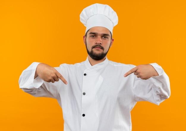 Zelfverzekerde jonge mannelijke kok in uniform van de chef-kok wijzend naar zichzelf geïsoleerd op oranje muur
